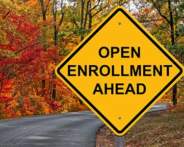 Road surrounded by trees with yellow sign that says Open Enrollment Ahead