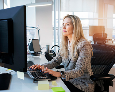 Women sitting in her office looking and typing on her computer