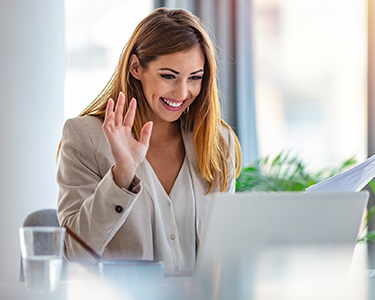 Woman waving at her computer
