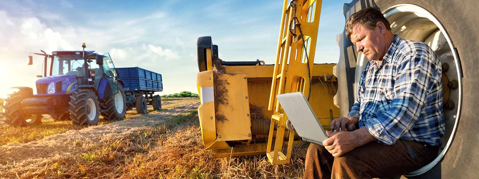A farmer uses a computer in the field